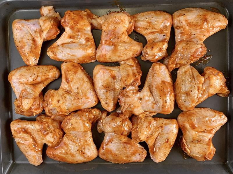 Chicken wings in a marinade on a baking sheet. Cooking chicken with spices in the oven. Fried Chicken Legs and Wings Recipe royalty free stock photo
