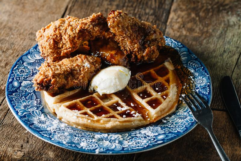 Chicken wings and waffles served with butter and blackberry syrup. Chicken wings and waffles served with butter on blue vintage plate royalty free stock photo