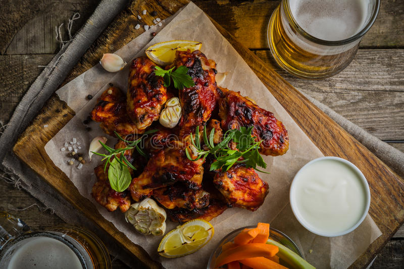 Chicken wings in on wood board. Chicken wings on wood board with beer and vegetable sticks royalty free stock images