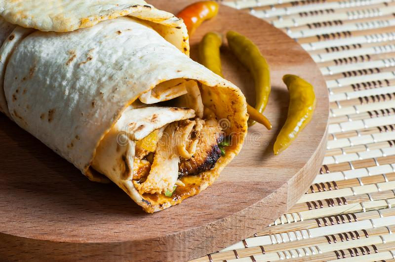 Chicken wrap doner kebap in lavash pita bread durum with thin green pepper pickle on wooden platter. Turkish shawarma, traditional food royalty free stock images