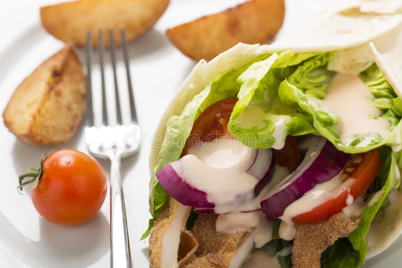 Chicken wrap with fresh vegetables and steak potatoes, on the pl stock photos