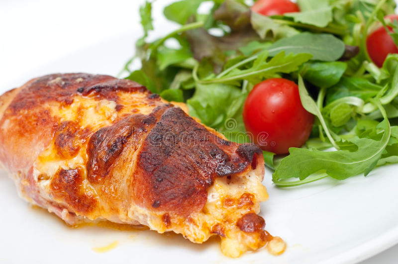 Chicken wrapped in bacon served with salad. Against white background stock image
