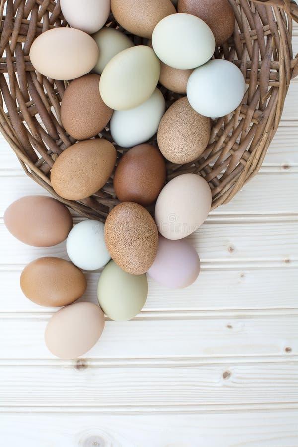 Chickeneggs orgánicos frescos en cesta polvorienta vieja en backgrou de madera foto de archivo