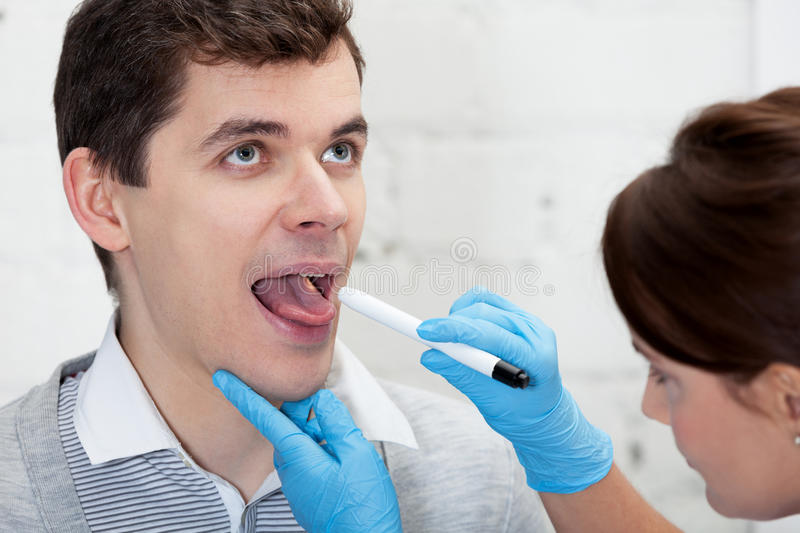 Chicking throat. Doctor is checking throat of a patient royalty free stock photos