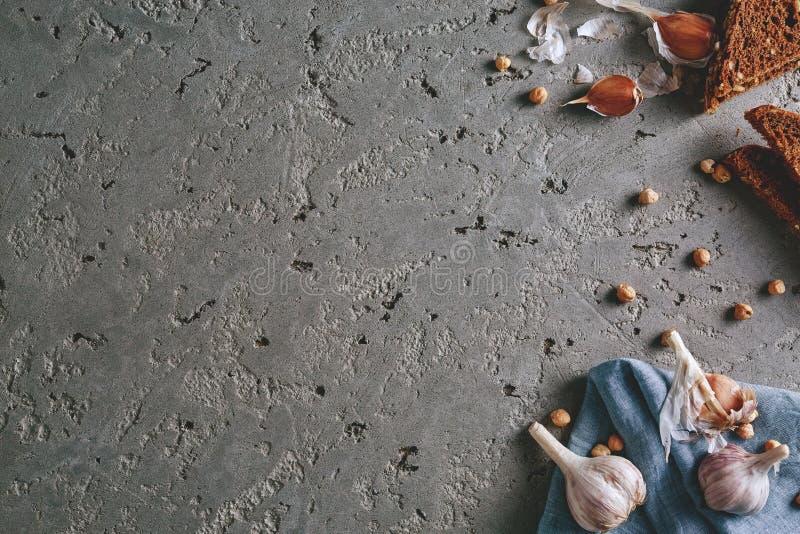 Chickpea, czosnku i całej banatki chleb na popielatym betonowym tle, zdjęcie royalty free