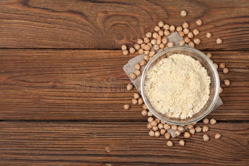 Chickpea flour in a wooden spoon royalty free stock photos