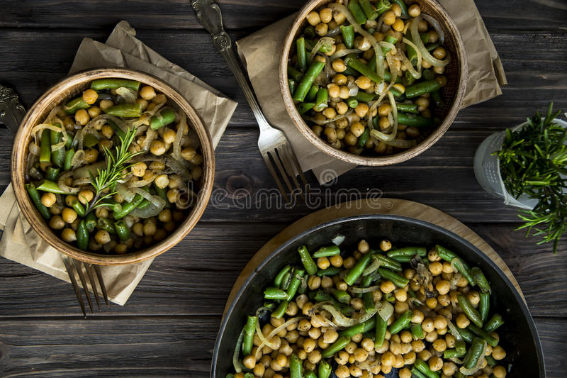 Chickpea stew with green beans and onion, seasoned with rosemary. vegan food. Carbohydrate food for dieting and healthy lifestyle royalty free stock photos