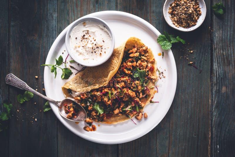 Chickpeas Crepe with Harissa Spicy Chicken, Kale, Cilantro and Yogurt Dukkah Sauce. On wooden background stock photos
