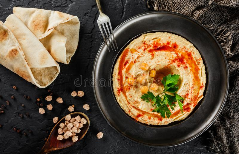 Chickpeas hummus με το ελαιόλαδο, πάπρικα σε ένα πιάτο πέρα από το σκοτεινό υπόβαθρο πετρών Υγιή vegan τρόφιμα, καθαρή κατανάλωση στοκ εικόνες