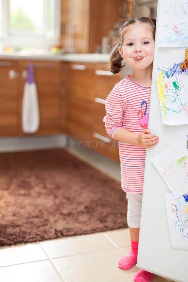 Chicle de la niña linda detrás de la puerta del refrigerador en cocina imagen de archivo libre de regalías