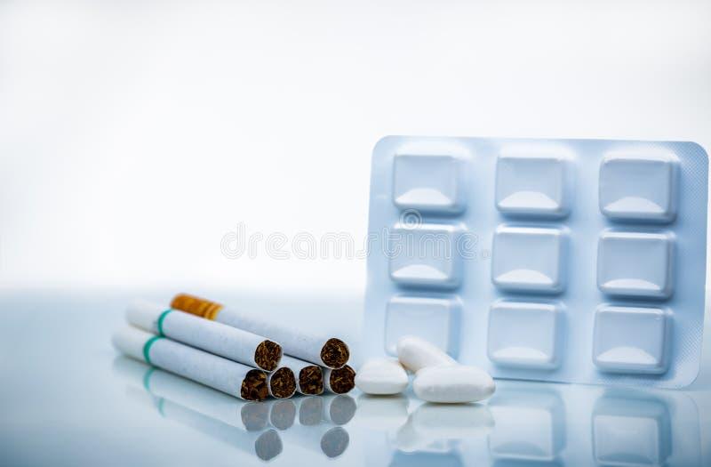 Chicle de la nicotina en paquete de ampolla cerca de la pila de cigarrillo Quit que fuma por la goma de la nicotina del uso para  foto de archivo