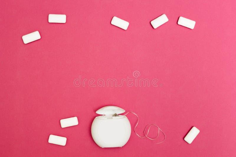 Chicle y seda dental en un fondo rosado Espacio para el texto fotografía de archivo