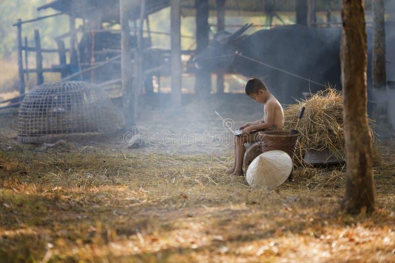 Chico del campo de Tailandia que se sienta en una pila de paja, y jugando el cuaderno del ordenador en fondo de la granja fotografía de archivo libre de regalías