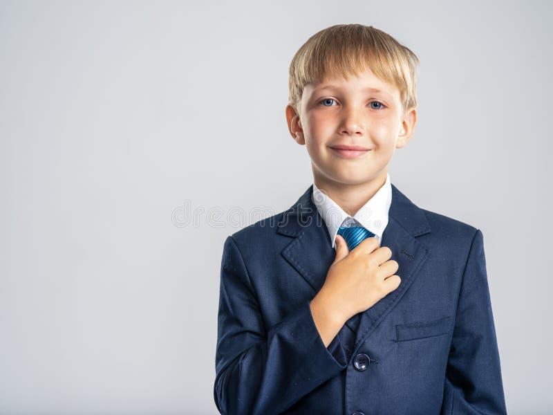 Chico rubio positivo vestido con traje formal que toca su corbata Retrato de un niño blanco sonriente con un traje de negocios az fotografía de archivo