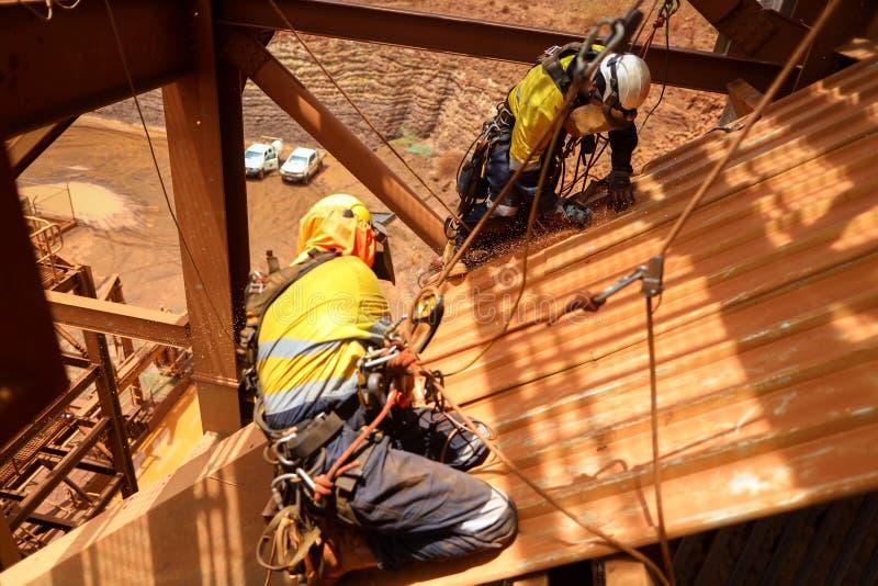 Chicote de fios de segurança vestindo da manutenção do acesso da corda, capacete que abseiling com as duas cordas que assentam a  imagens de stock