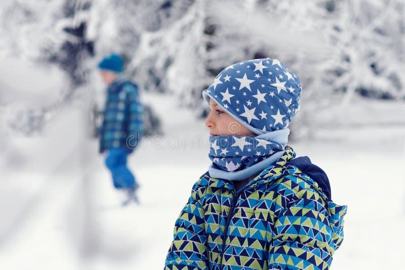 Chidlren i vinter parkerar i snö royaltyfri fotografi