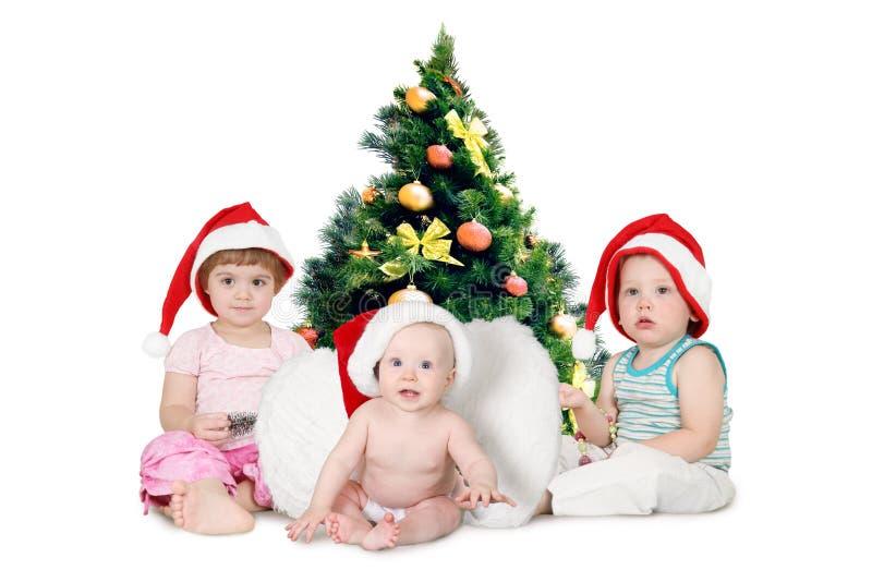 Chidren in Kerstmishoeden dichtbij bont-Boom stock afbeelding