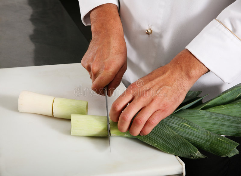 Chief carve onion. Leek on professional kitchen royalty free stock photo