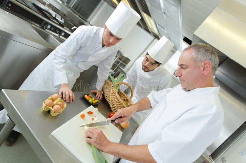 Chief chef teaching assistants in restaurant kitchen stock image