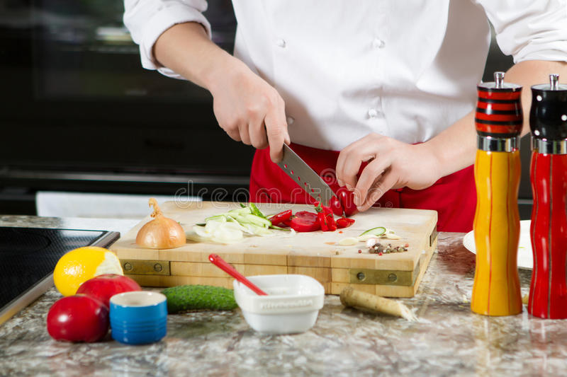 Chief cook cut the tomato with the knife in kitchen stock image