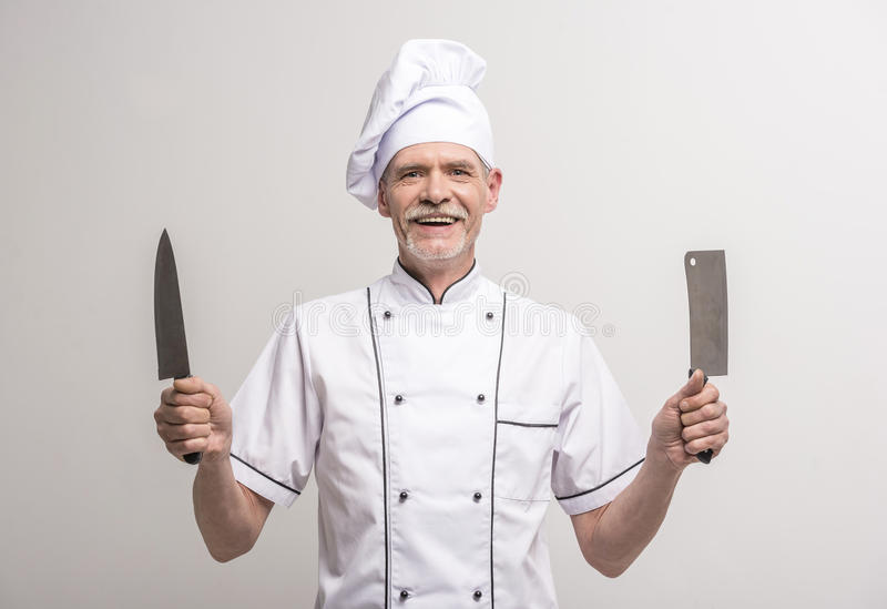 Chief cook. Senior male chief cook in uniform holding knifes a on grey background stock photography