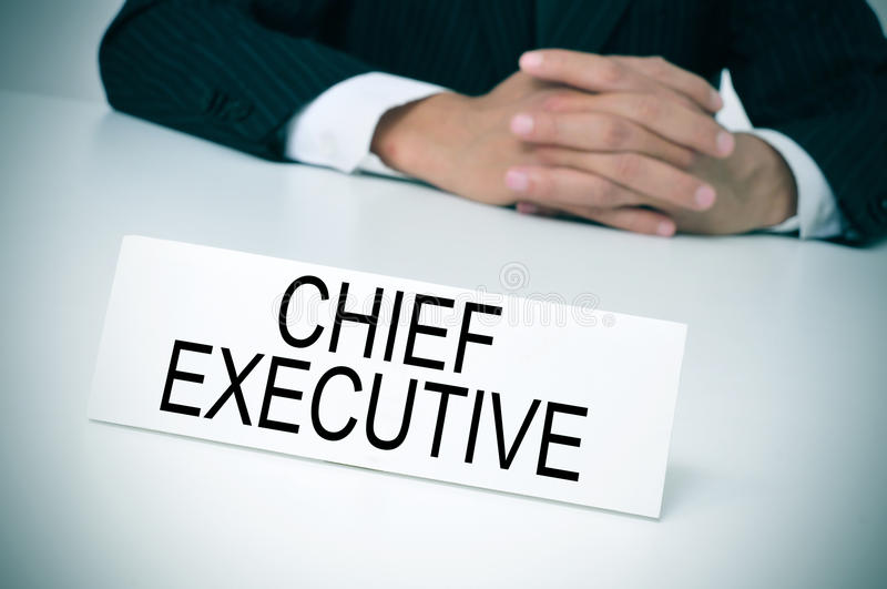 Chief executive in his office. A man in suit sitting at a desk with a signboard in front of him with the text chief executive written in it stock photography