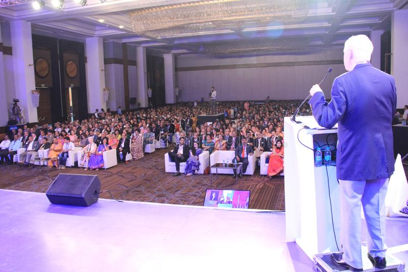 Speaker addressing a house full of conference audience. Chief Guest standing on stage dais and speaking to delegates in a conclave of Rotary International Club royalty free stock image