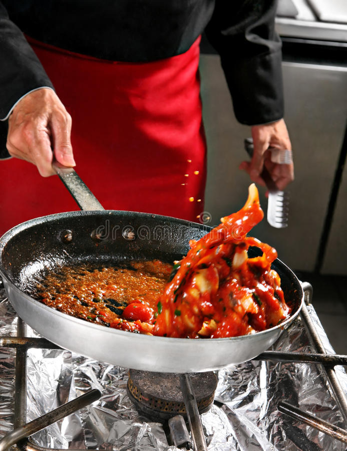 Chief shaking food. Chief shaking fried food in pan royalty free stock image