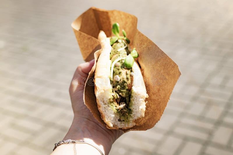 Chien chaud végétarien avec saucisse de soja à la main féminine à un festival de rue image stock