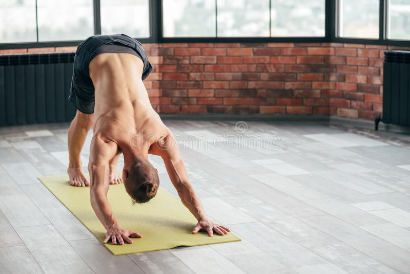 Chien de haut en bas d'épine de yoga d'homme arrière en bonne santé de sport image libre de droits