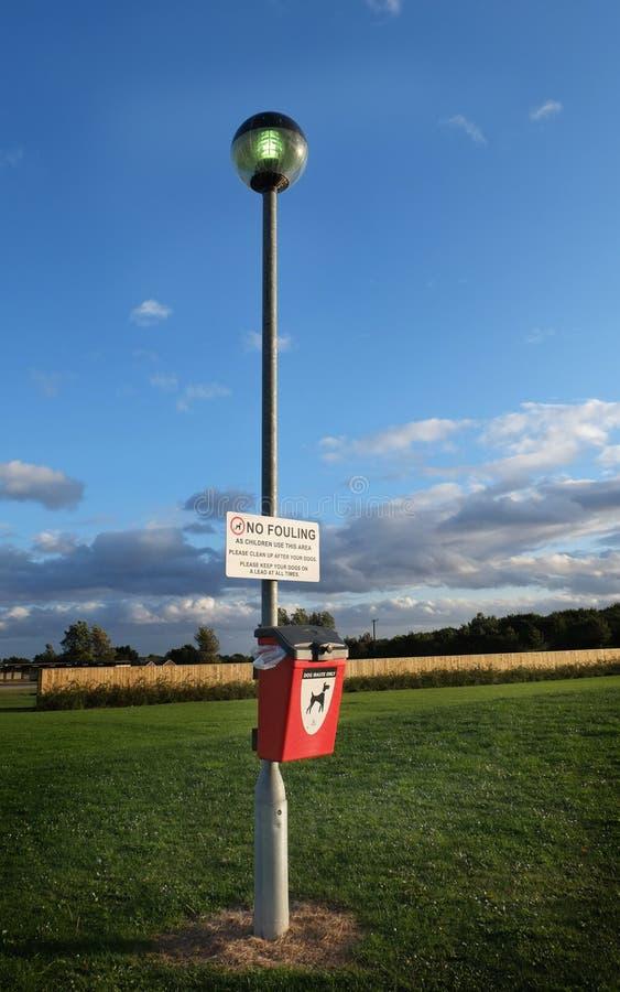 Chien encrassant le signe et la poubelle photographie stock libre de droits