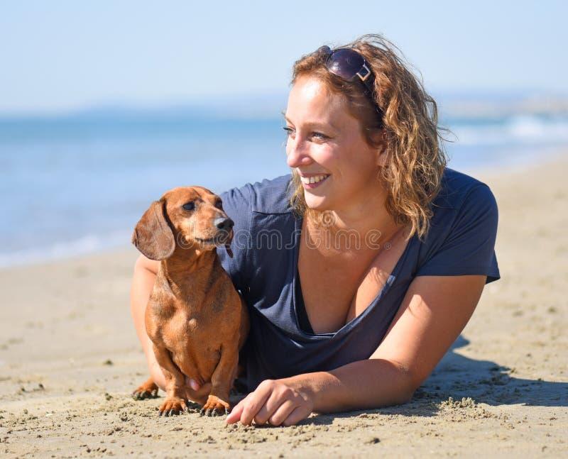 Chien et femme sur la plage photo stock