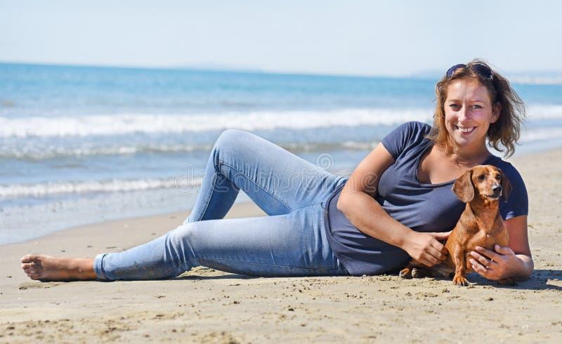 Chien et femme sur la plage photographie stock