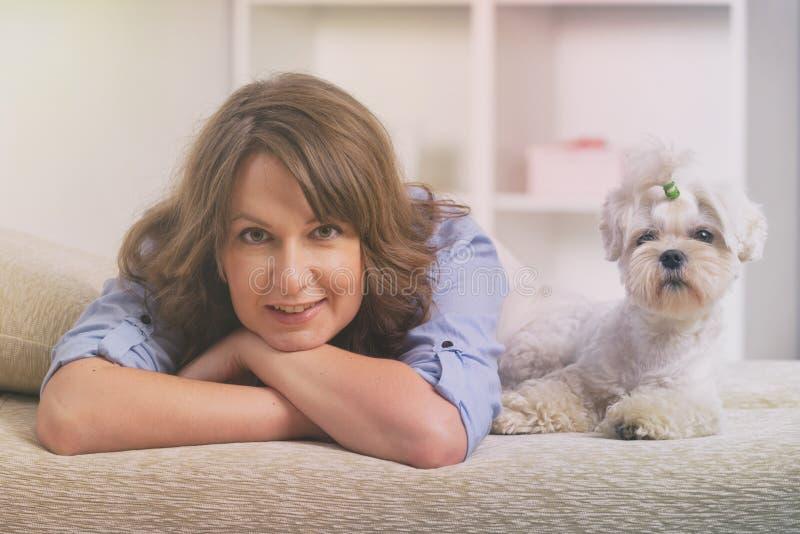 Chien et propriétaire sur le sofa dans la maison photographie stock