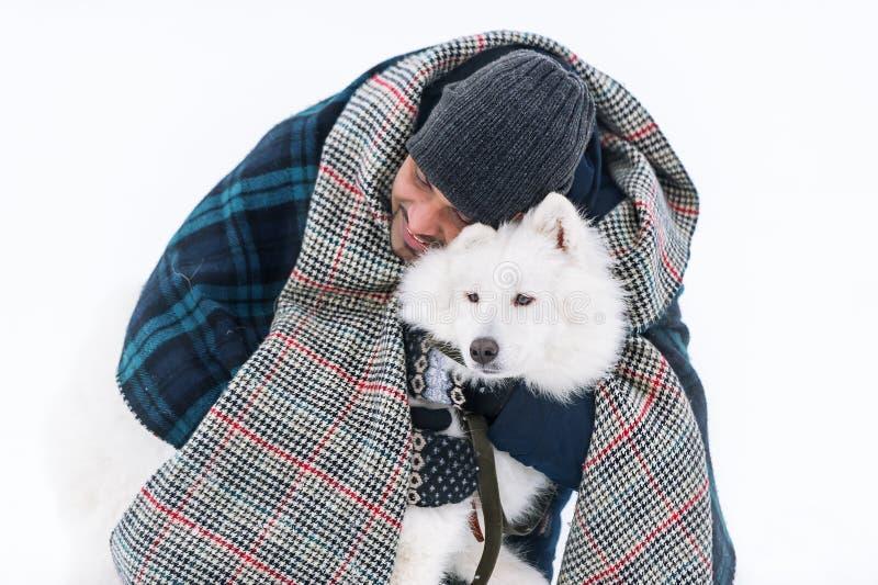 Chien pelucheux blanc solide de jeune embrassement sri-lankais d'homme en hiver images stock