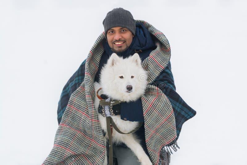 Chien pelucheux blanc solide de jeune embrassement sri-lankais d'homme en hiver Foyer sélectif chez le chien photos stock