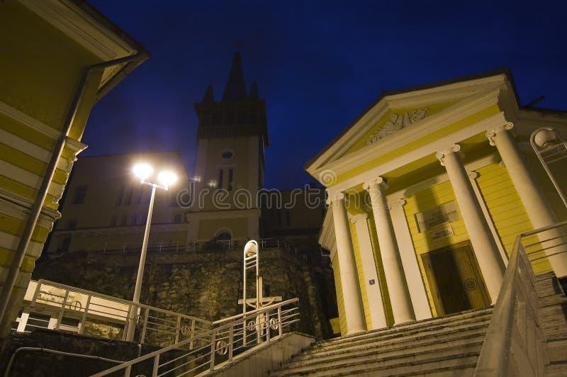 Chiesa cattolica in mezzo dei buidlings della città fotografia stock