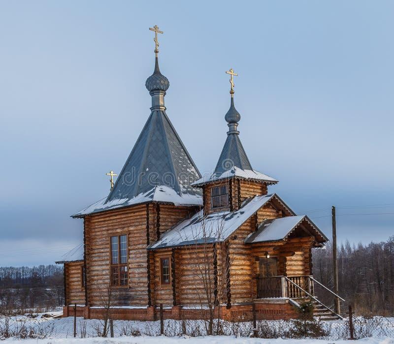 Chiesa di legno in un settore coperto di neve fotografia stock libera da diritti