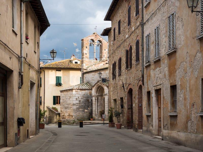 """Chiesa di pietra antica in San Quirico D """"Orcia, vecchio villaggio medievale nelle colline toscane fotografia stock libera da diritti"""