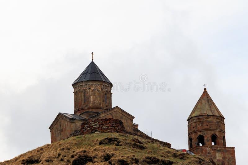 Chiesa di trinità di Gergeti Tsminda Sameba, chiesa di trinità santa vicino al villaggio di Gergeti in montagne caucasiche, Georg fotografia stock libera da diritti