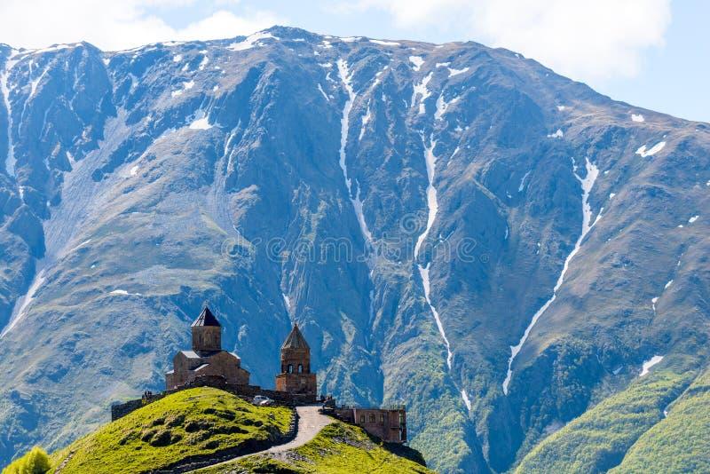 Chiesa di trinità ortodossa nel villaggio di Gergeti contro il contesto delle montagne, Caucaso immagine stock