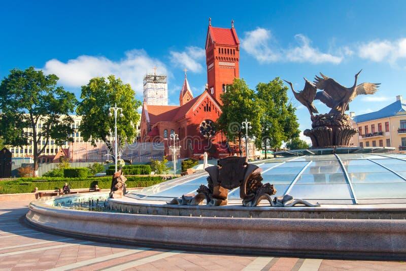 Chiesa e fontana rosse al quadrato di indipendenza a Minsk, Bielorussia fotografie stock libere da diritti