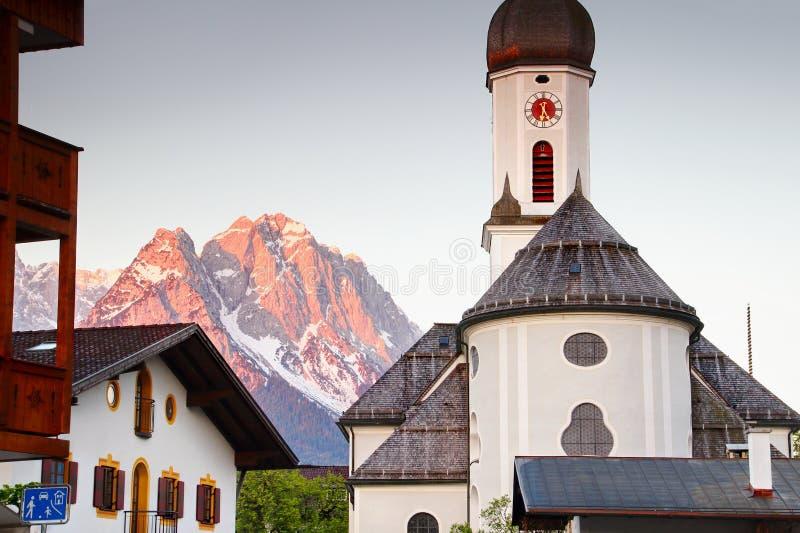 Chiesa in Garmisch con il picco di Zugspitze alla luce solare rossa di mattina immagine stock libera da diritti