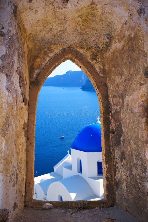Chiesa greca tradizionale attraverso una vecchia finestra in Santorini immagini stock libere da diritti