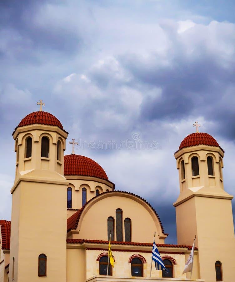 Chiesa greco ortodossa con le nuvole di tempesta che si riuniscono sopra  fotografia stock
