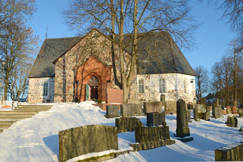 Chiesa luterana medievale nel vecchio giorno di Sunny February del cimitero della città Halikko, Finlandia fotografia stock