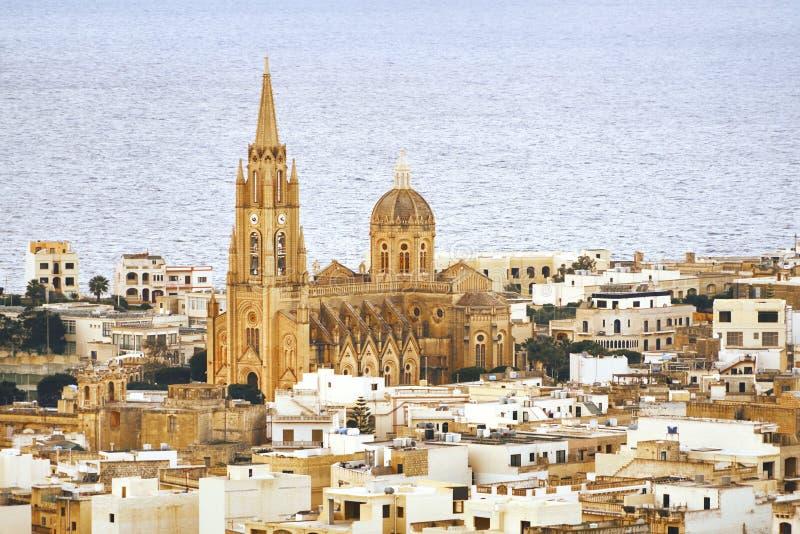 Chiesa in mezzo alla città sui precedenti del mare immagine stock