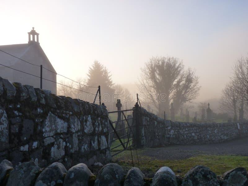Chiesa nebbiosa e cimitero immagine stock