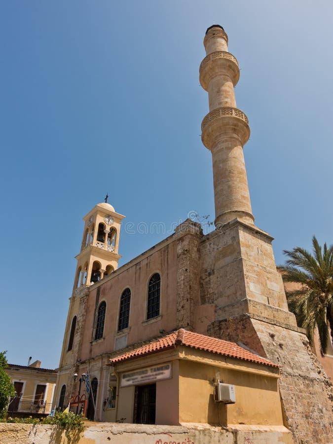 Chiesa ortodossa e moschea musulmana parallelamente al vecchio porto veneziano, città di Chania, isola di Creta fotografie stock