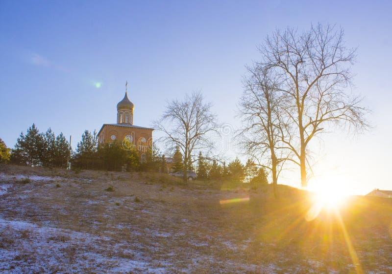 Chiesa ortodossa su una collina vicino al paesaggio di tramonto di inverno della foresta con i chiari raggi del sole e del cielo  fotografie stock